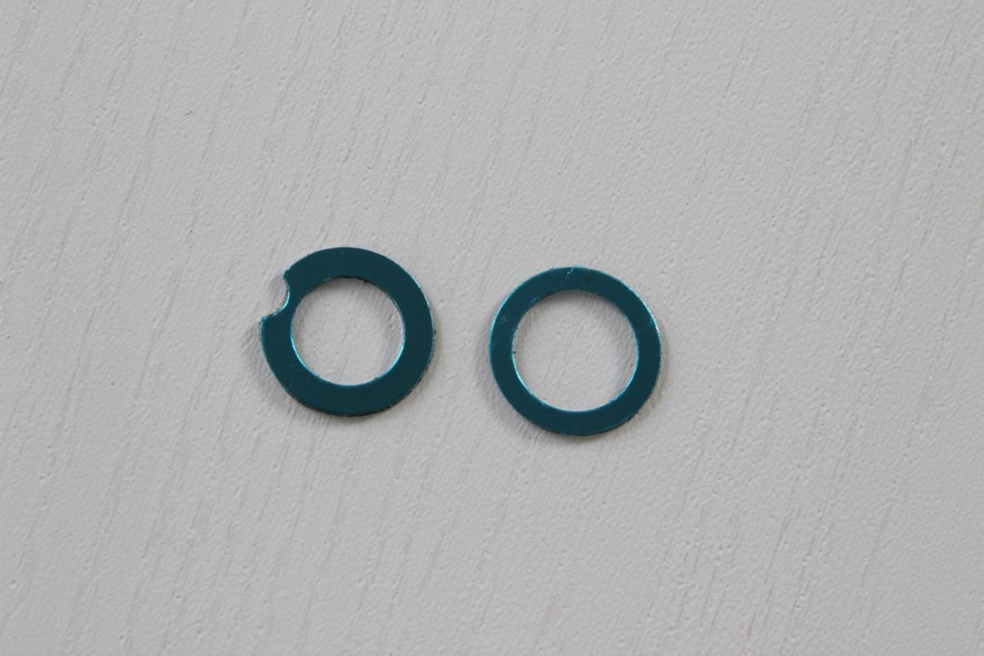 These metal rings have a sticky back for attaching to the cell phone (non-permanent). They are shaped a bit differently - the one with the notch could be used if the flash is close to the lens, so that it will not cover it.